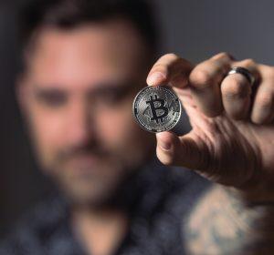 person-holding-silver-bitcoin-coin